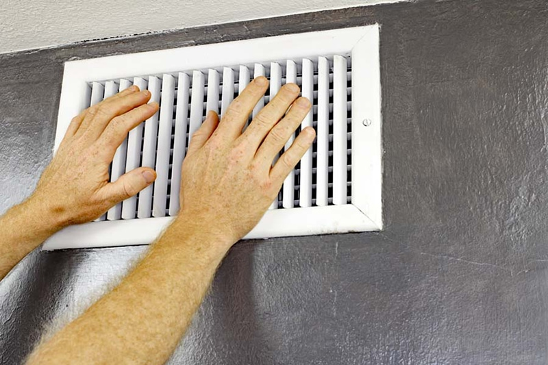 a pair of adult male hands feeling the flow of air coming out of ac vent, ac unit blowing hot air