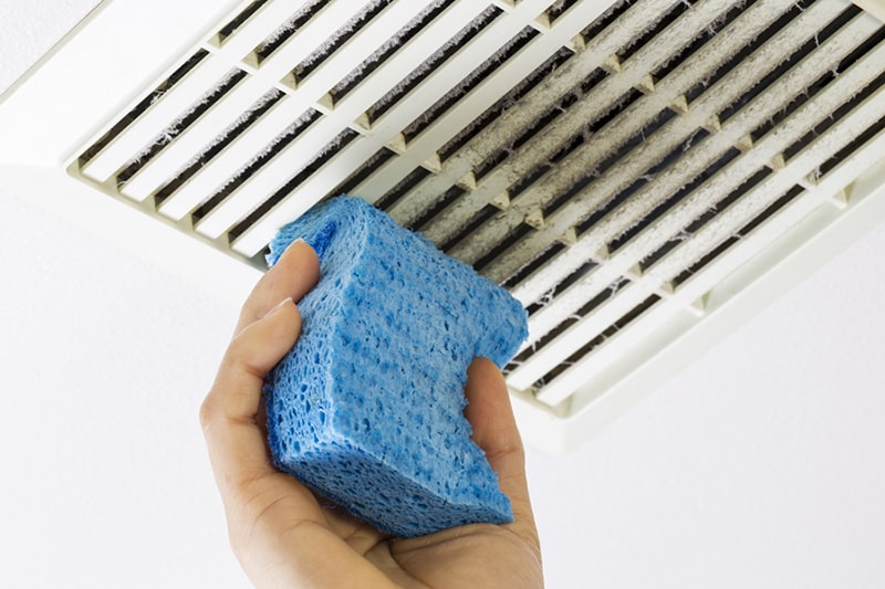 Why Air Duct Cleaning Is Important, Close up horizontal photo of female hand cleaning dirty bathroom fan vent cover with blue sponge